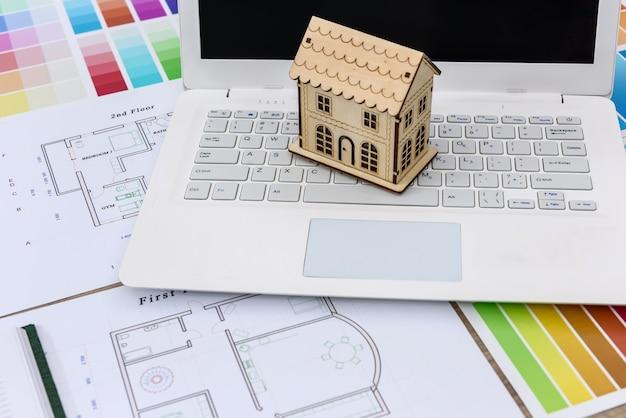 Laptop, plan, model drewnianego domu i próbki kolorów na drewnianym biurku