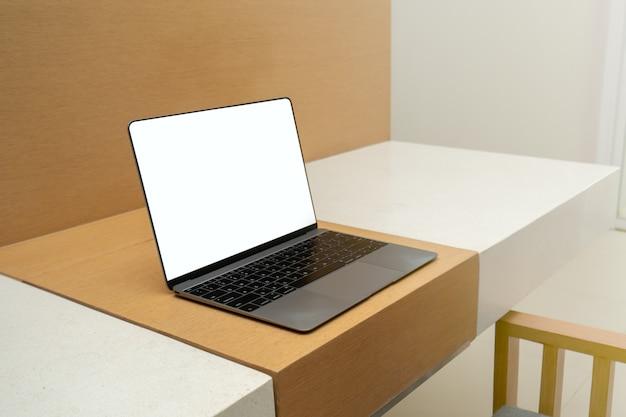 Laptop pokazuje pusty biały ekran na drewnianym stole.