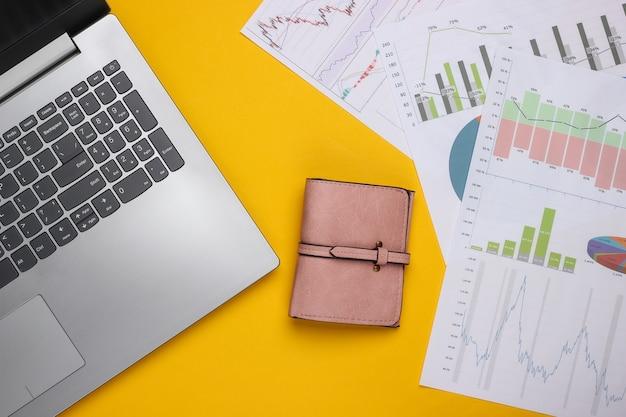 Laptop, portfel z wykresami i wykresami na żółtym tle. biznesplan, analityka finansowa, statystyki. widok z góry