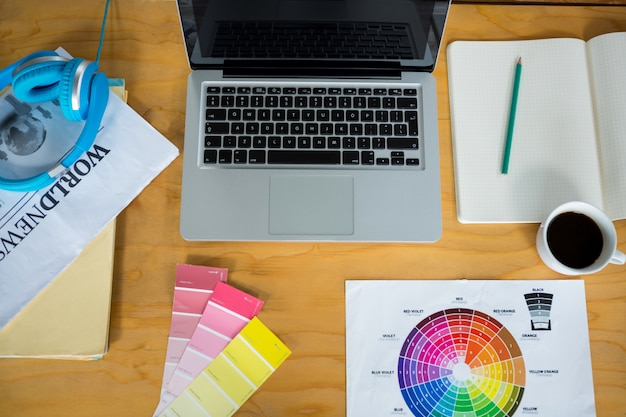 Laptop, próbka koloru i słuchawki na biurku