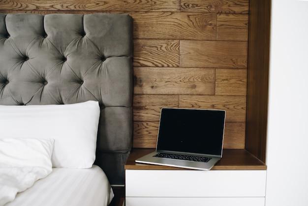 Laptop przy łóżku, praca z domu wczesnym rankiem