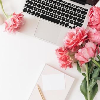 Laptop, pusta kartka papieru, kwiaty tulipanów różowej piwonii na białym stole