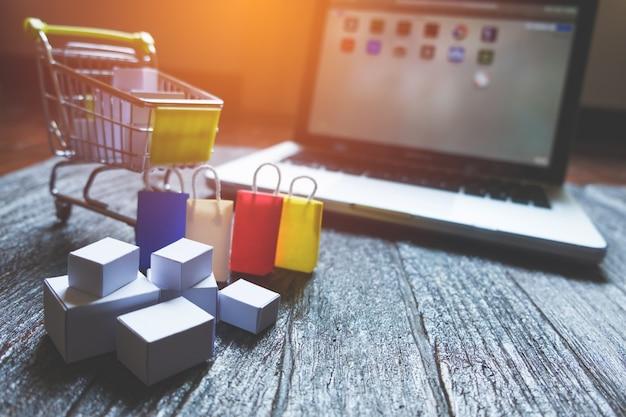 Laptop pusty ekran i hopping koszyk pełen prezentów z copyspace, koncepcja zakupów online
