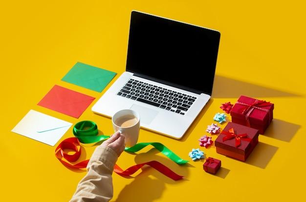 Laptop, ręka trzymająca filiżankę kawy i różne rzeczy związane z bożym narodzeniem