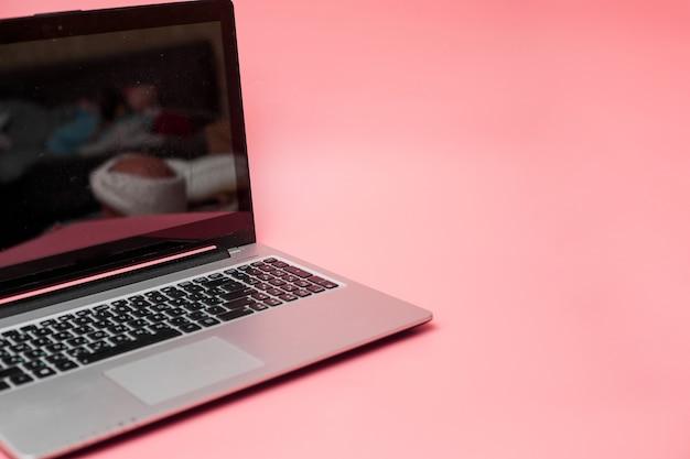 Laptop, różowe tło, baner, kopia przestrzeń