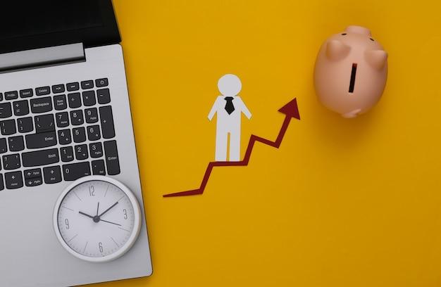 Laptop, skarbonka, zegar i papierowy człowiek na strzałce wzrostu.