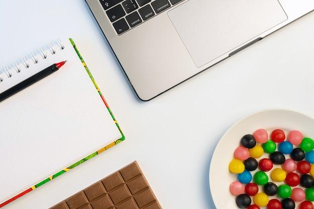 Laptop, słodycze i skoroszyt z barem czekolady i kawy w miejscu pracy.