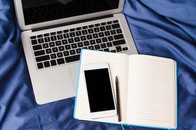 Laptop, smartfon i notebook na łóżku w czasie rano. makieta.
