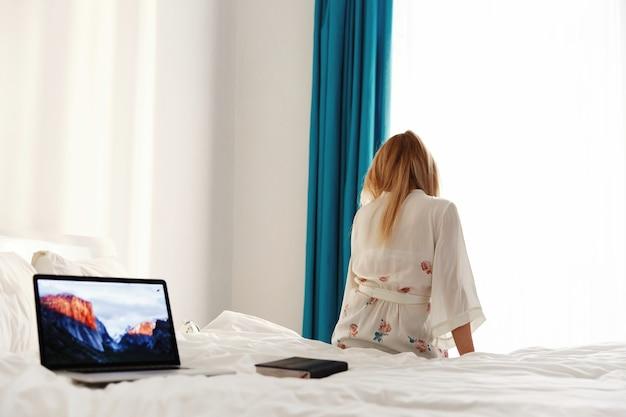 Laptop stoi na białym łóżku, podczas gdy kobieta siedzi na nim przed oknem