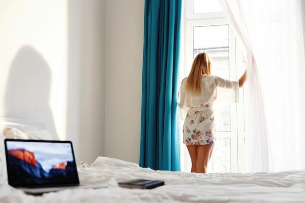 Laptop stoi na białym łóżku, podczas gdy kobieta stoi przed oknem