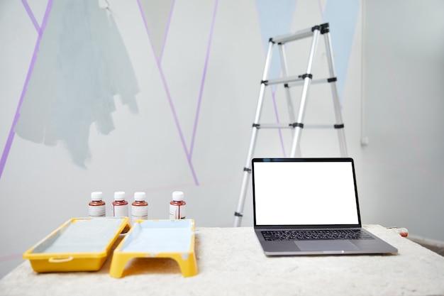 Laptop stojący na stole z białą makieta przestrzeni kopii ze ścianą malowaną na drabinie w tle