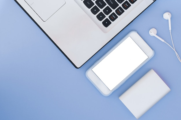 Laptop, telefon, słuchawki i power bank na niebieskim tle. kompozycja flat lay i miejsce na tekst. widok z góry.