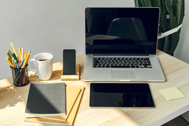 Laptop w jasnym pokoju na stole roboczym z materiałów biurowych