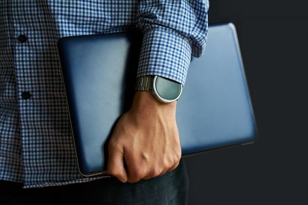 Laptop w ręku.