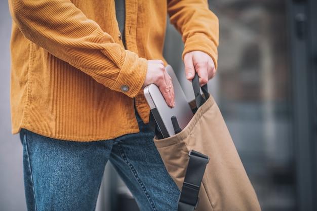 Laptop w torbie. zbliżenie dłoni mans umieszczenie laptopa w torbie
