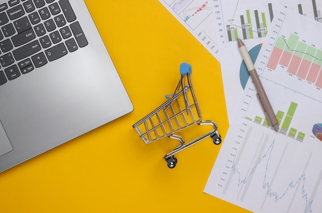 Laptop, wózek na zakupy z wykresami i wykresami na żółtym tle. biznesplan, analityka finansowa, statystyki. widok z góry