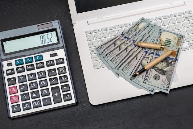 Laptop z banknotami dolara na czarnej powierzchni