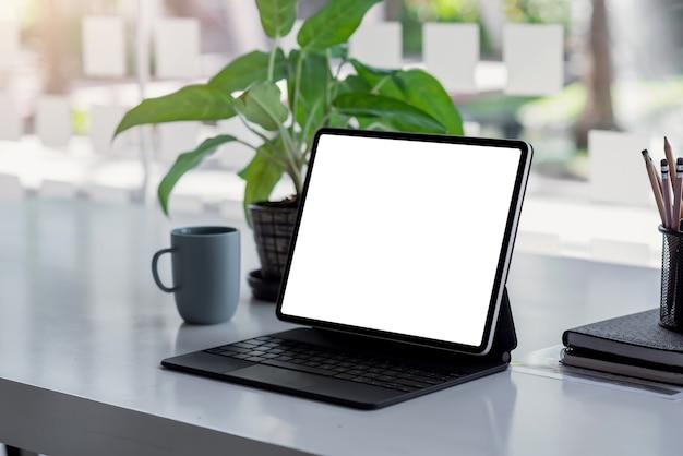 Laptop z białym ekranem i czarną klawiaturą na stole i zielonymi drzewami. makieta