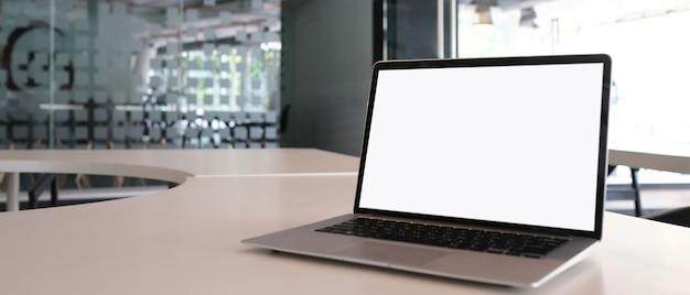 Laptop z białym ekranem na białym stole i kopia przestrzeń z tłem biurowym.