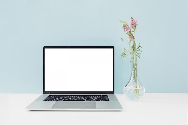 Laptop z białym pustym ekranem i kwiatami w wazonie na stole na niebiesko. makieta