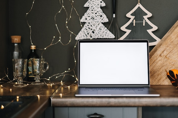 Laptop z białym pustym ekranem makiety, na stole w kuchni z dekoracją świąteczną.
