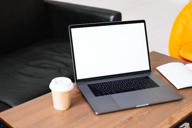 Laptop z białym pustym ekranem makiety, na stole w salonie.