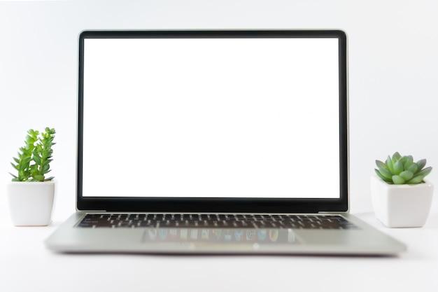 Laptop z białym pustym ekranem na białym tle z małą rośliną i gadżetem.