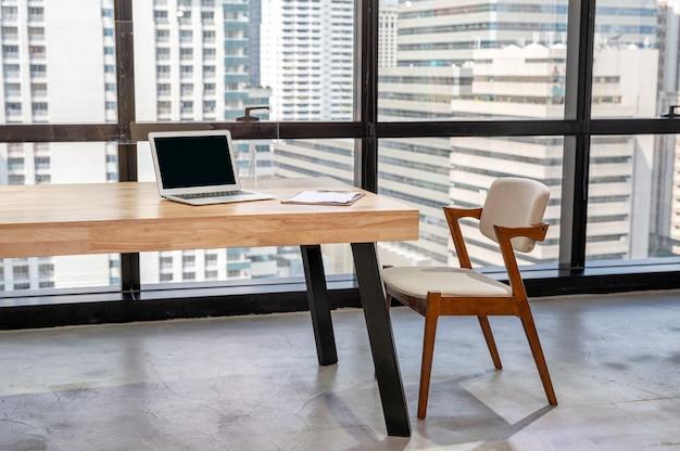 Laptop z biznesowym dokumentem na drewnianym biurku i krześle w biurze