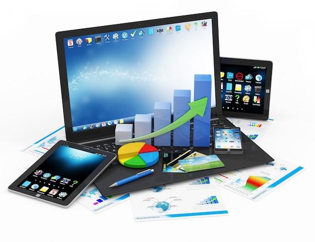 Laptop z biznesowym wykresem kołowym i smartfonem obok tabletu i raportów finansowych