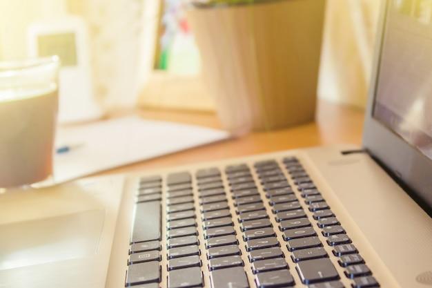 Laptop z bliska klawiatury i filiżankę gorącej kawy rano. selektywna ostrość.
