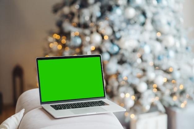 Laptop z chromakey z zielonym ekranem w pobliżu ozdób choinkowych