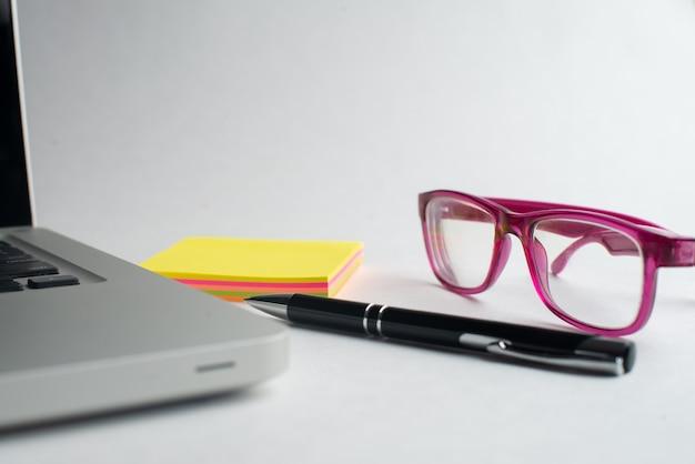 Laptop z czarnym długopisem i kolorowymi notatnikami, fioletowe okulary na biurku