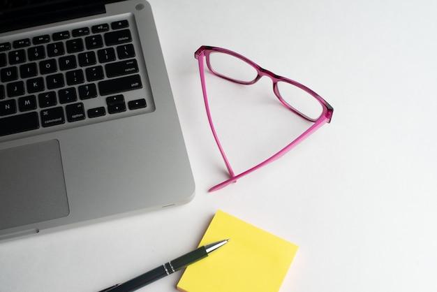 Laptop z czarnym długopisem i kolorowymi notatnikami, okulary na biurku