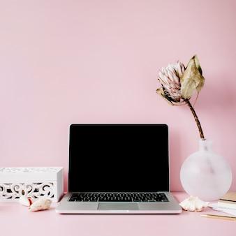 Laptop z czarnym ekranem na stole z kwiatem proteus i dekoracją