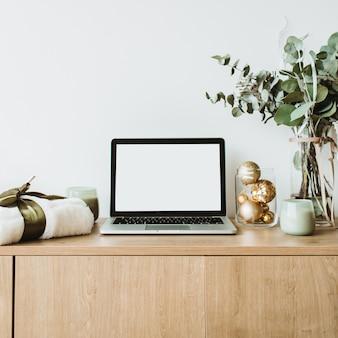 Laptop z ekranem na drewnianym biurku ozdobionym bukietem eukaliptusa, pudełkiem prezentów, świecami na białej powierzchni.
