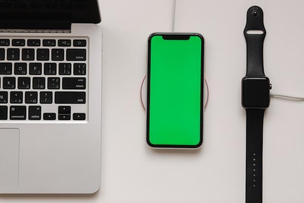 Laptop z inteligentnym zegarkiem i ładowaniem telefonu na bezprzewodowej ładowarce. zielony ekran w telefonie, ekranowy wskaźnik ładowania na zegarku. widok z góry. miejsce na tekst