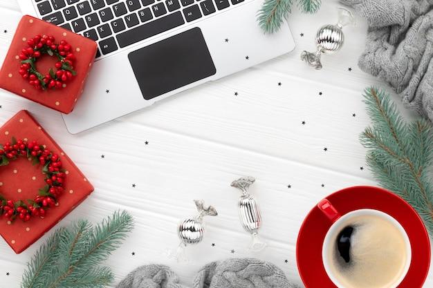 Laptop z kawą i prezentami na białym drewnie. boże narodzenie mieszkanie leżało