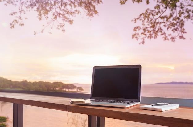 Laptop z książką notatek na stole w kawiarni z widokiem na morze. praca na zlecenie