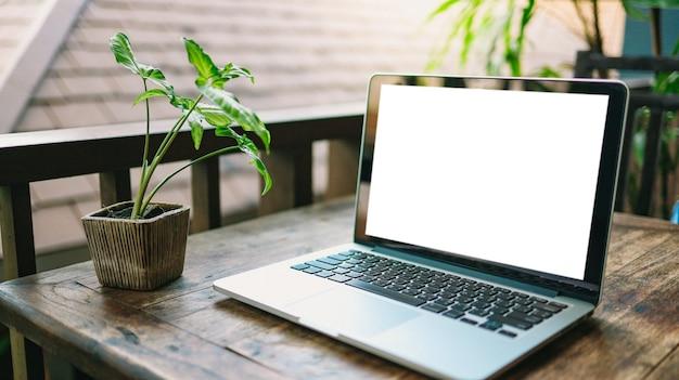 Laptop z makiety pusty ekran na drewnianym stole przed kawiarnią na tekst. wyświetlacz produktu montaż laptopa komputer - technologia koncepcja pracy niezależnej