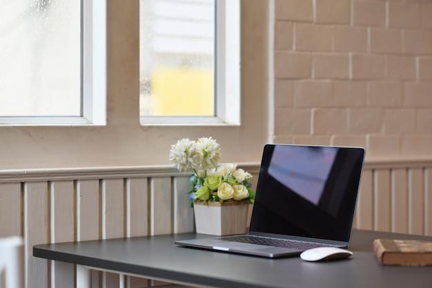 Laptop z materiały biurowe i gadżety na drewnianym stole