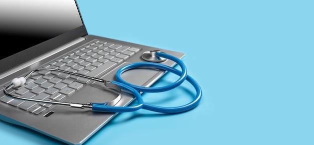 Laptop z medycznym oprogramowaniem diagnostycznym i stetoskopem. stetoskop i laptop na białym tle na niebieskim tle. koncepcja telezdrowia