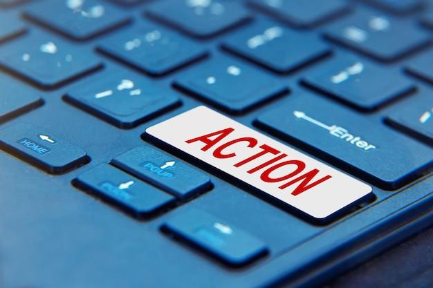 Laptop z napisem action słowo na przycisku klawiatury