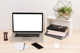 Laptop z notatnikami na drewnianym stole