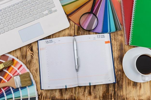 Laptop z notatnikiem i próbką koloru przy stole