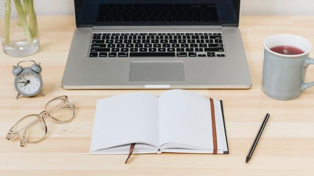 Laptop z notatnikiem na drewnianym stole