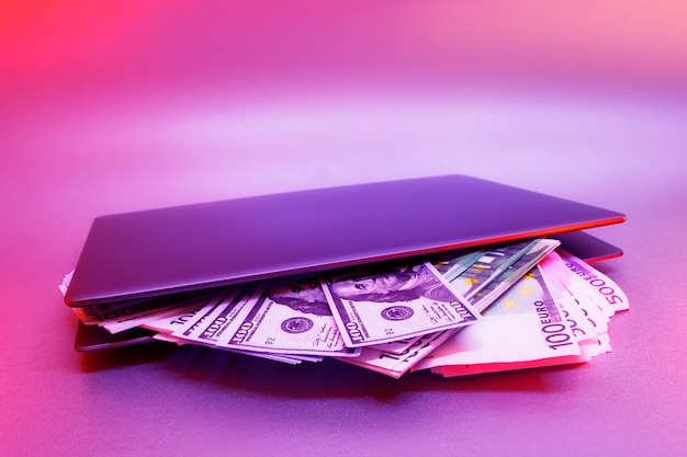 Laptop z pakietami dolarów i euro na tle kolorowych jasnych neonowych niebieskich i fioletowych świateł uv.