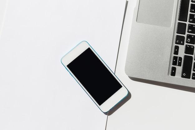 Laptop z pastylką i smartphone na biel ściany zakończeniu up