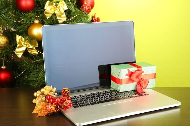 Laptop z prezentami na stole na zielonym tle