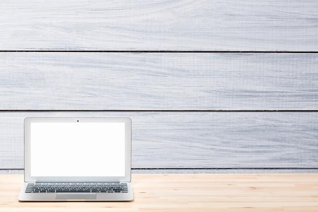 Laptop z pustym białym ekranem na jasnym drewnianym stole na szarej drewnianej ścianie lub powierzchni.