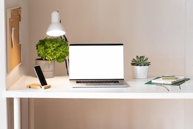 Laptop z pustym białym ekranem na wnętrzu biurka. stylowy widok tabeli makieta pracy w kolorze różowego złota.